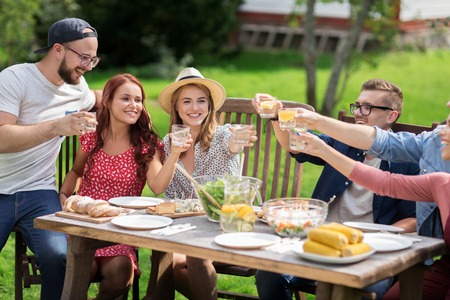 home and garden: leisure, holidays, eating, people and food concept - happy friends clinking glasses and celebrating at summer garden party