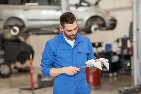 Auto-Service, Reparatur, Wartung und Menschen Konzept - Automechaniker Mann oder Schmied mit dem Schraubenschlüssel an der Werkstatt Standard-Bild - 65132107