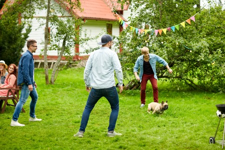 leisure, holidays, people and pets concept - happy friends playing with dog at summer garden party Standard-Bild