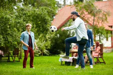 cottage: leisure, holidays, people and sport concept - happy friends playing football at summer garden party