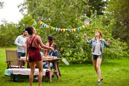 レジャー、休日、人々、スポーツ コンセプト - 夏の園遊会でバドミントンや羽根を遊んで幸せな友達