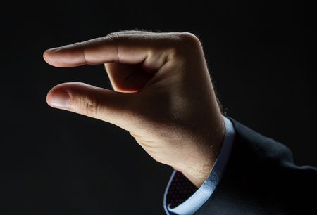 tiny: business, people, sign language and gesture concept - close up of businessman hand showing small size over black background