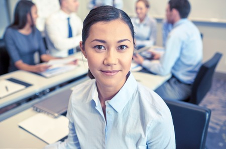 teamwork people: business, people and teamwork concept - smiling businesswoman with group of businesspeople meeting in office