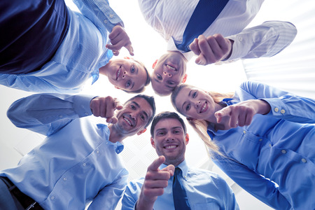 business, people and teamwork concept - smiling group of businesspeople standing in circle