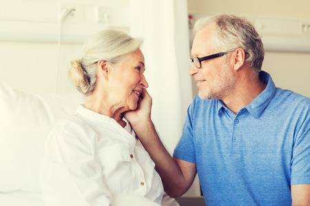 cheering people: medicine, age, support, health care and people concept - happy senior man visiting and cheering his woman lying in bed at hospital ward Stock Photo