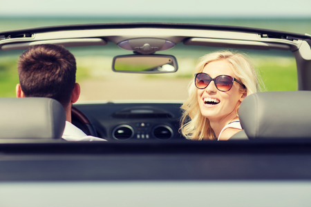couple dating: transport, road trip, leisure, couple and people concept - happy man and woman driving in cabriolet car outdoors