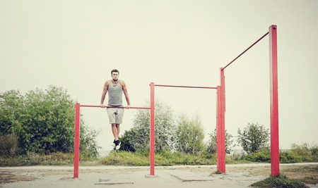 gripping bars: fitness, sport, training and lifestyle concept - young man exercising on horizontal bar outdoors