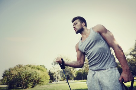 calisthenics: fitness, sport, exercising, training and lifestyle concept - young man exercising with expander in summer park