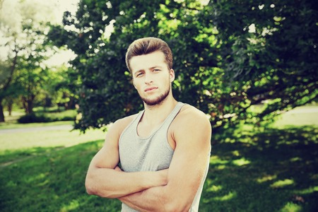 fitness, sport, people and healthy lifestyle concept - sporty young man with crossed arms at summer park Stock Photo