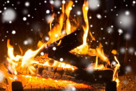 winter, christmas, warmth, fire and coziness concept - close up of firewood burning in fireplace with snow