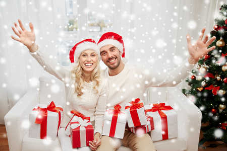 hispanic girl: christmas, holidays and people concept - happy couple in santa hats with gift boxes sitting on sofa at home