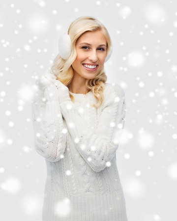 winter fashion: winter, fashion, christmas and people concept - smiling young woman in earmuffs and sweater Stock Photo