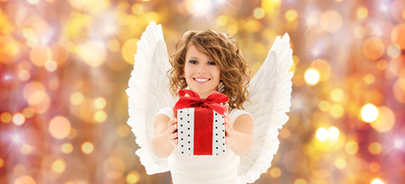 angel birthday: people, holidays, christmas and birthday concept - happy young woman with angel wings holding gift box over lights background