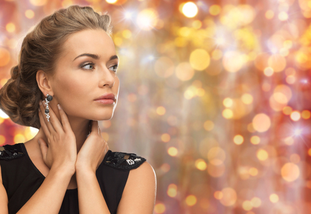 beauty woman: beauty, luxury, people, holidays and jewelry concept - beautiful woman with gem stone earrings over lights background Stock Photo