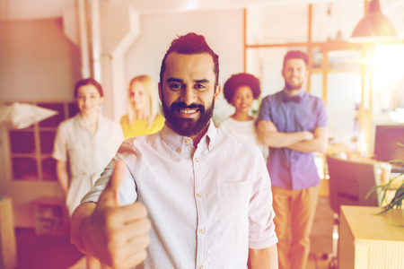 success man: business, startup, people, success and teamwork concept - happy young man with beard over creative team showing thumbs up in office
