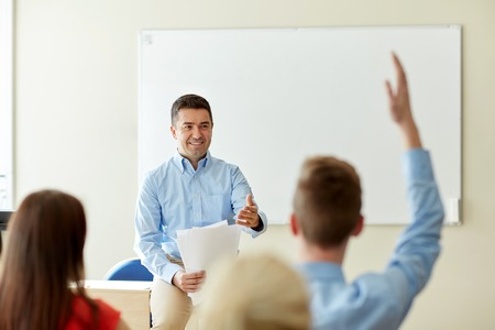 school classroom: education, school and people concept - group of happy students and teacher with papers or tests Stock Photo