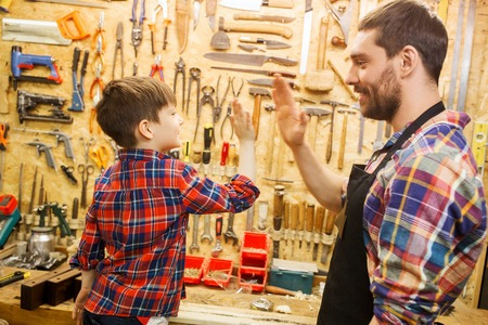 woodworker: family, carpentry, woodwork, gesture and people concept - happy father and little son making high five at workshop Stock Photo