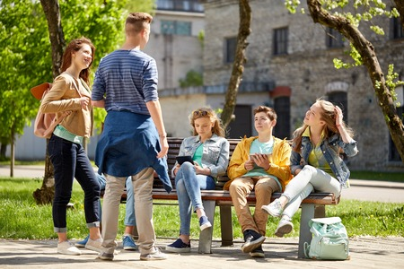 sitting people: education, high school and people concept - group of happy teenage students with tablet pc computers sitting on bench at campus yard