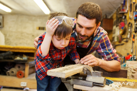 family, carpentry, woodwork and people concept - father and little son working with wood plank at workshop
