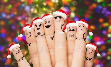 smile face: family, holidays, christmas and body parts concept - close up of fingers with smiley faces and santa hats over lights background