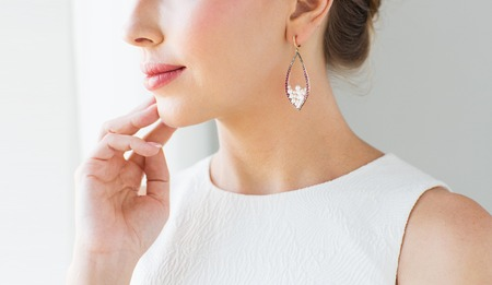 glamour luxury: glamour, beauty, jewelry and luxury concept - close up of beautiful woman face with pearl earring Stock Photo