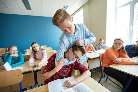 education, bullying, violence, aggression and people concept - student boy suffering of classmate mockery Фото со стока