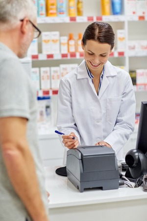 pharmaceutics: medicine, pharmaceutics, health care and people concept - smiling pharmacist writing check and senior man at drugstore cash register
