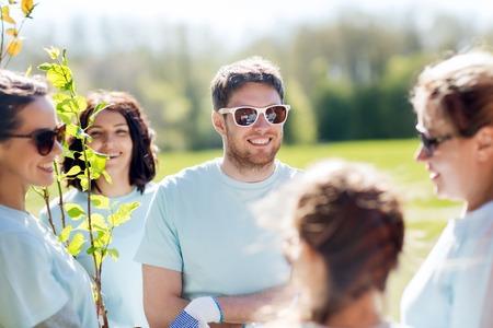 vrijwilligerswerk, liefdadigheid, mensen en ecologie concept - groep vrijwilligers het planten van bomen in park