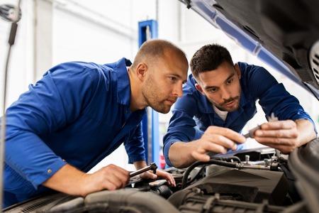 services automobiles, la réparation, l'entretien et les gens concept - hommes mécaniques avec une clé de réparation de voiture à l'atelier