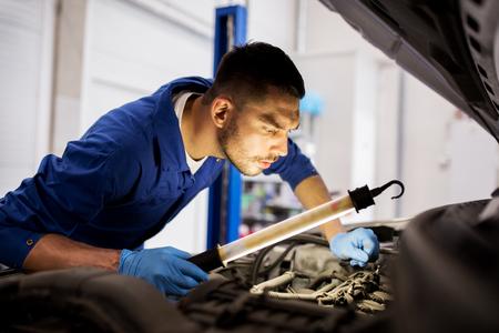 자동차 서비스, 수리, 유지 관리 및 사람들이 개념 - 자동차 정비공 남자 워크샵에서 램프 작업