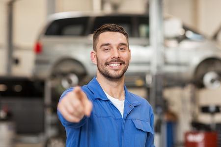 車サービス、修理、保守および人々 のコンセプト - オート メカニック マニュアルまたはワーク ショップでスミスを笑って幸せです