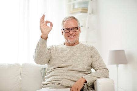 buen vivir: la vejez, el gesto, la comodidad y el concepto de la gente - hombre mayor sonriente con gafas sentado en el sofá y que muestra la muestra de la mano bien en casa