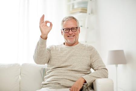 old age, gesture, comfort and people concept - smiling senior man in glasses sitting on sofa and showing ok hand sign at home Stockfoto