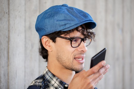 using voice: leisure, technology, communication and people concept - smiling hipster man using voice command recorder or calling on smartphone at street wall