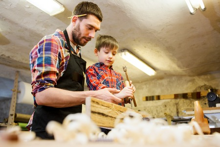 woodworker: family, carpentry, woodwork and people concept - father and little son with hammer and chisel working with wood plank at workshop Stock Photo