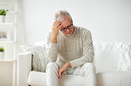Gezondheid, pijn, stress, ouderdom en mensenconcept - senior man die hoofdpijn heeft thuis