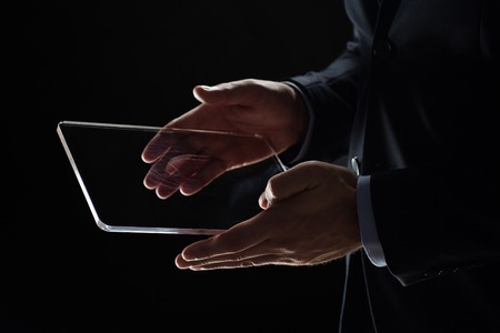 business, people and future technology concept - close up of businessman hands with transparent tablet pc computer over black
