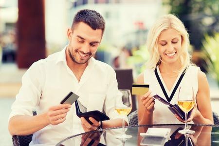 pagando: fecha, las personas, el pago y el concepto de independencia financiera - pareja feliz con tarjetas de crédito en carteras y copas de vino que paga la cuenta en el restaurante Foto de archivo