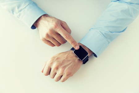 business concept: business, technology and people concept - close up of male hands setting smart watch at home Stock Photo