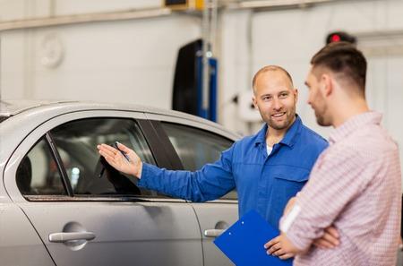services automobiles, la réparation, l'entretien et les gens concept - mécanicien avec presse-papiers montrant fenêtre du côté de l'homme ou le propriétaire au magasin de voiture