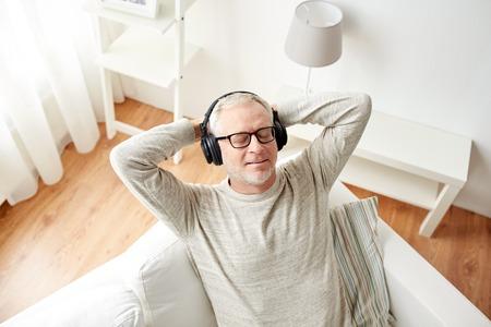 La tecnologia, le persone e concetto di lifestyle - felice l'uomo anziano in cuffie che ascolta la musica a casa Archivio Fotografico - 64929455