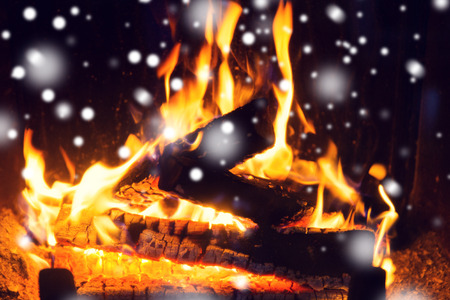 coziness: winter, christmas, warmth, fire and coziness concept - close up of firewood burning in fireplace with snow