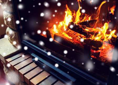 coziness: winter, christmas, warmth, fire and coziness concept - close up of burning fireplace at home with snow