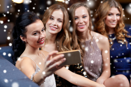 celebration, friends, bachelorette party, technology and christmas holidays concept - happy women with smartphone taking selfie at night club over snow
