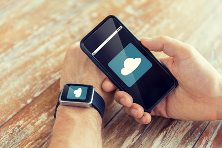 close icon: business, computing, technology and people concept - close up of male hand holding smart phone and wearing watch with cloud icon on screen at home