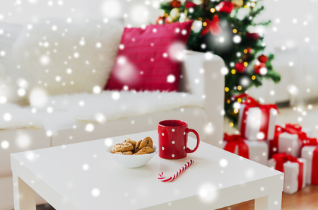 galletas: christmas, holidays, winter and celebration concept - close up of oat cookies, sugar cane candy and red cup on table at home Foto de archivo