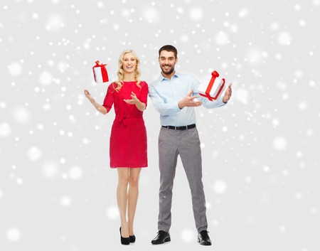 young happy couple: people, christmas, winter, couple and holidays concept - happy young man and woman playing with gift boxes over snow background Stock Photo