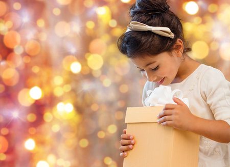 filipino people: holidays, presents, christmas, childhood and people concept - smiling little girl with gift box over lights background Stock Photo