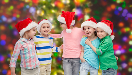 childhood, christmas, holidays, friendship and people concept - group of happy smiling little children in santa hats hugging over holidays lights background Stock Photo