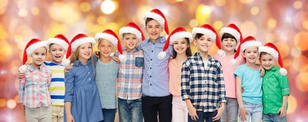 happy christmas: childhood, christmas, holidays and people concept - happy smiling children in santa hats hugging over lights background Stock Photo